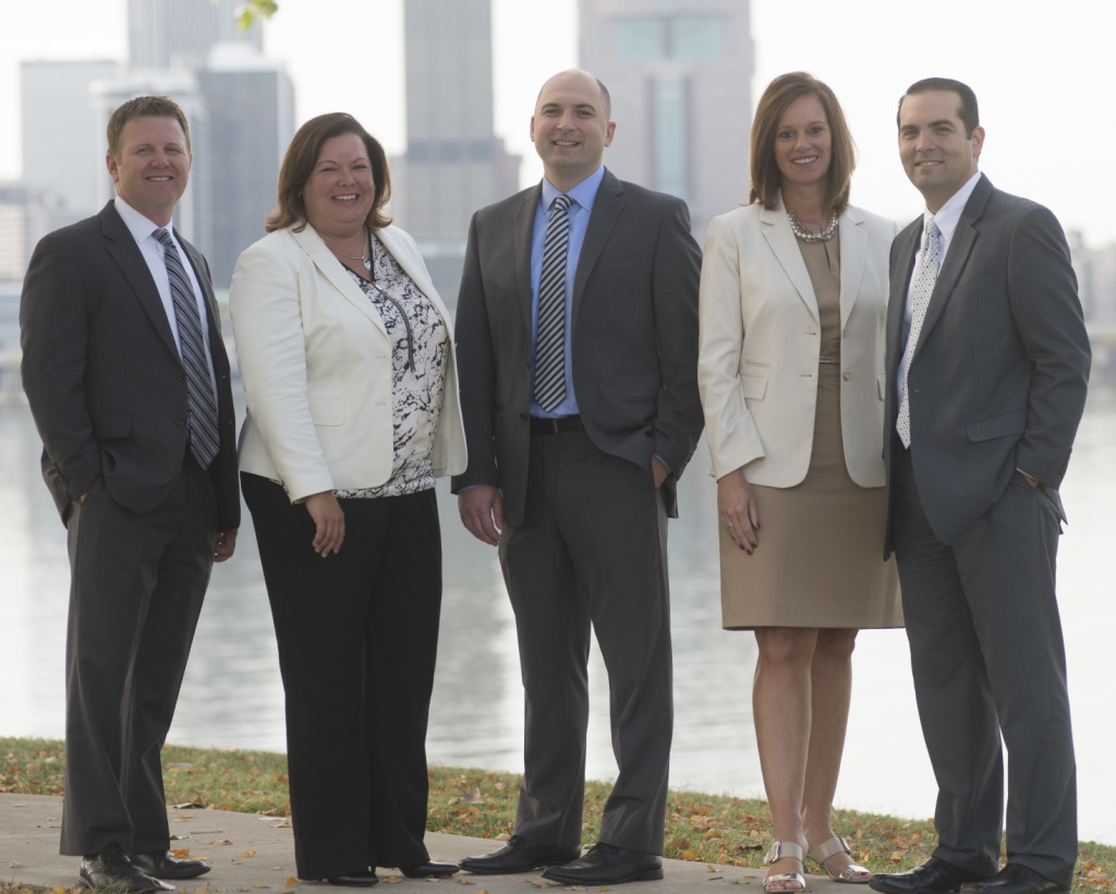 HSC management team members from various departments with Louisville skyline in the background.